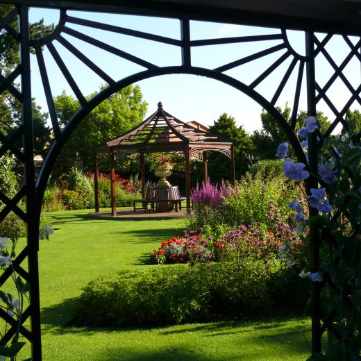Wooden Gazebo framed by a Garden Pergola