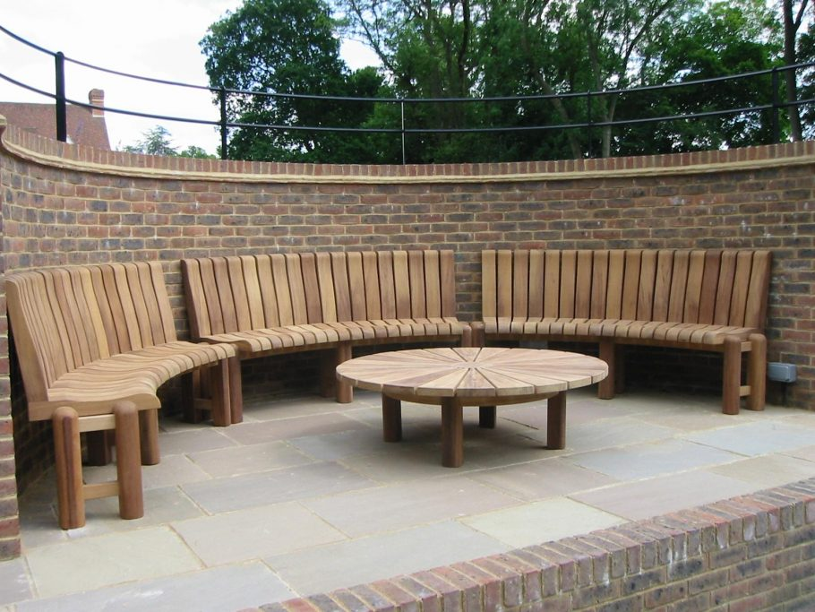 Bespoke curved wooden bench to fit inside a curved spectator area in a set of tennis courts