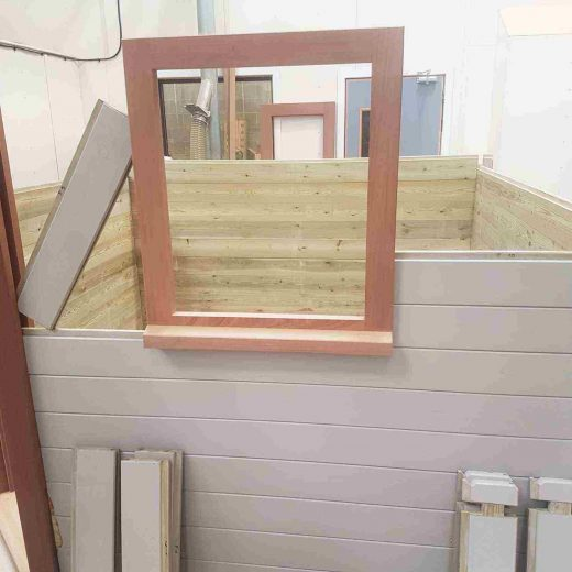 Constructing the walls of the wooden cabin and fitting the window