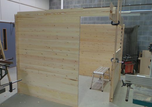Constructing the walls of the wooden cabin showing doorway forming