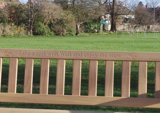Wooden bench memorial inscription: Take a seat with Walt and enjoy the view