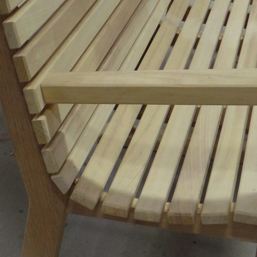 Close up showing the curve of the seat slats of the Regent wooden bench