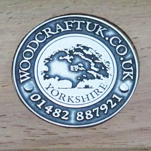 Steel embossed badge inset into wood