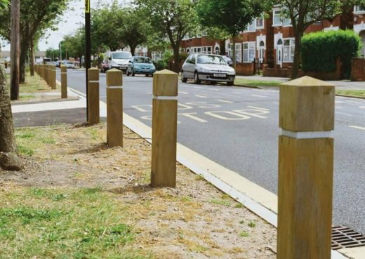 Roadside wooden bollards protecting grass verges from car parking